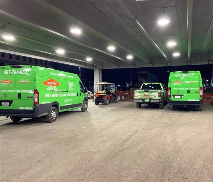 2 green SERVPRO vehicles in a parking lot with other vehicles