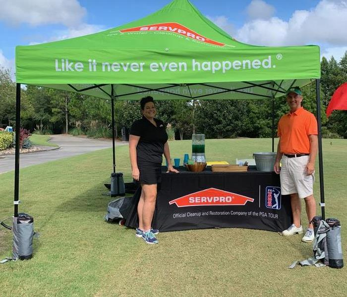 a man and a woman on a golf course by a SERVPRO tent