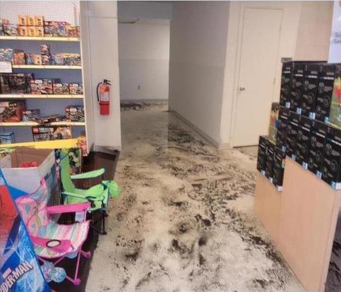 A warehouse with water and mud all over the floor after a storm