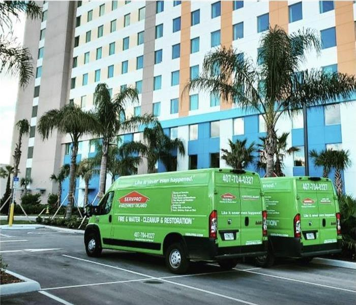 Two SERVPRO vans parked in the outside of a building